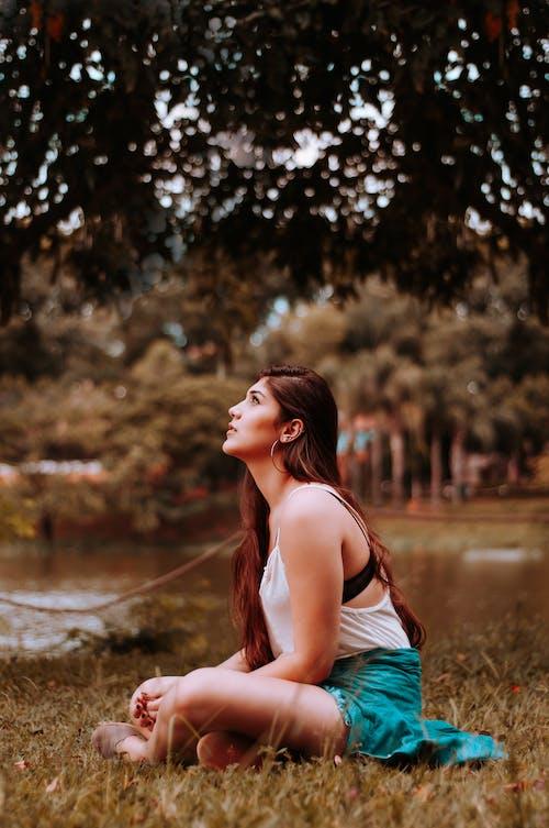 Woman Sitting on Grass Looking Upwards Near Tree