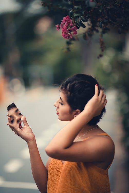 Woman Wearing Orange Cami Top Holding Mirror
