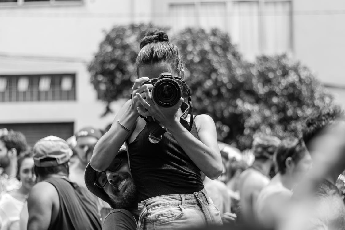 Grayscale Photography Of Man Carrying Woman While Taking Picture