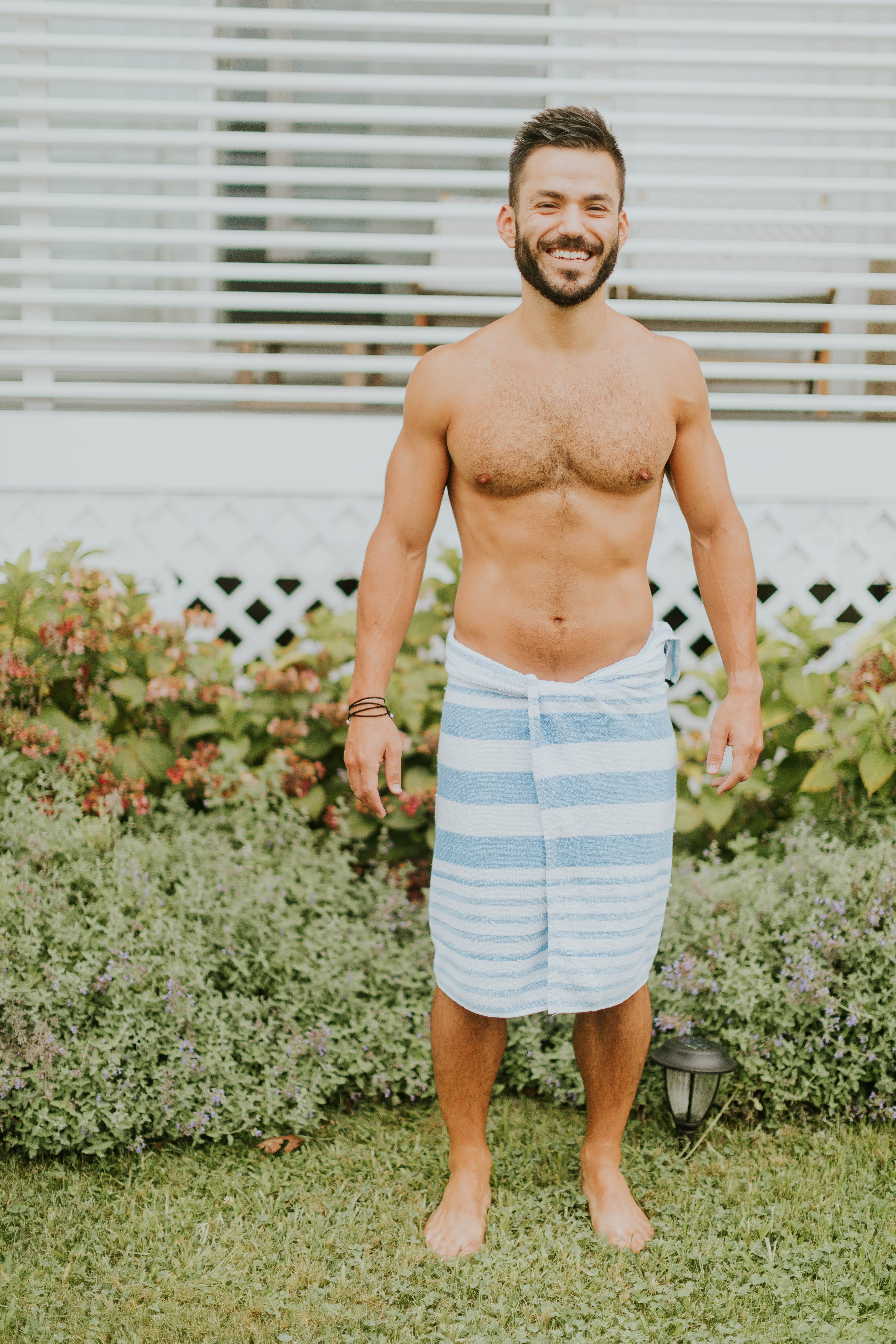 Man Standing With Towel On His Near Bush