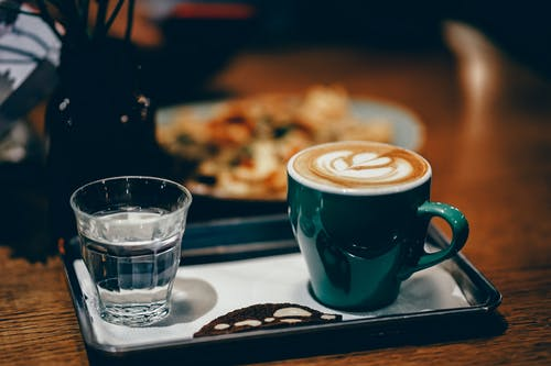 Чашка латте рядом с чашкой воды