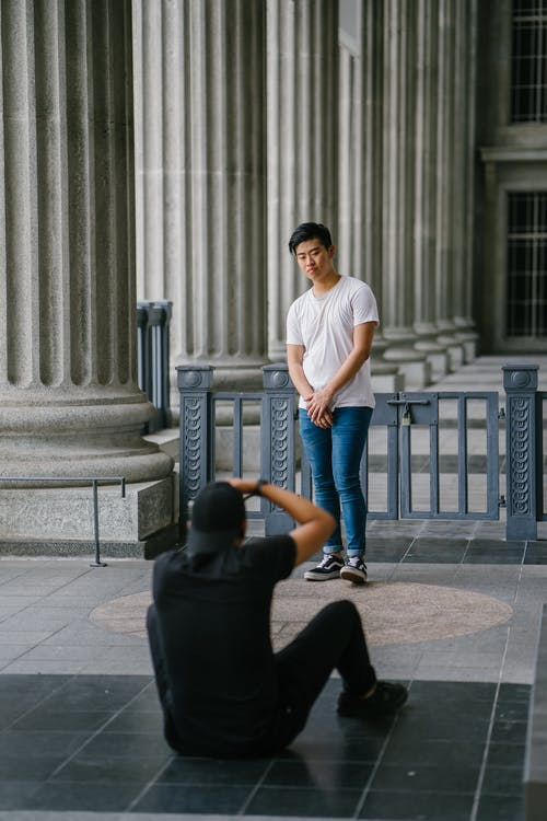 Man Sitting While Taking Picture Of Another Man