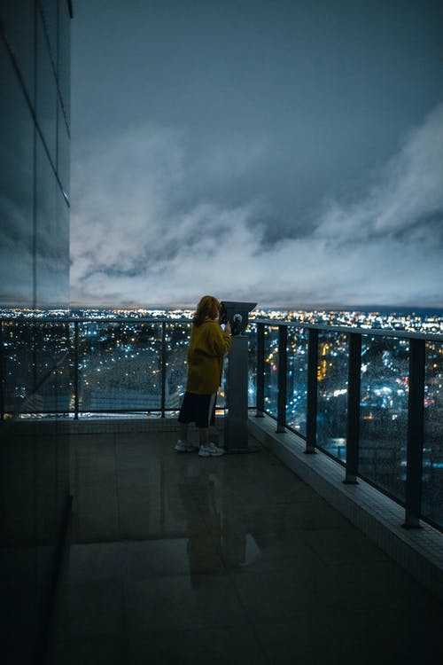 Woman in Yellow Sweater Looking at the Lighted City