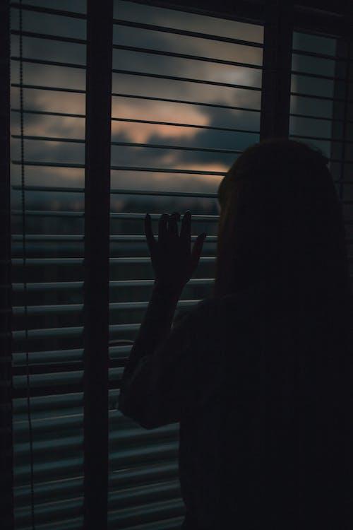 Силуэт женщины, глядя в окно