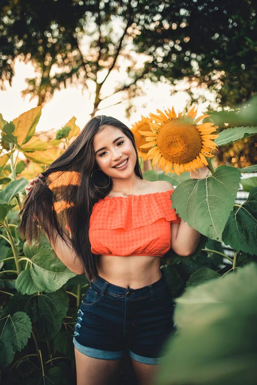Woman Smiling Near Sunflowers