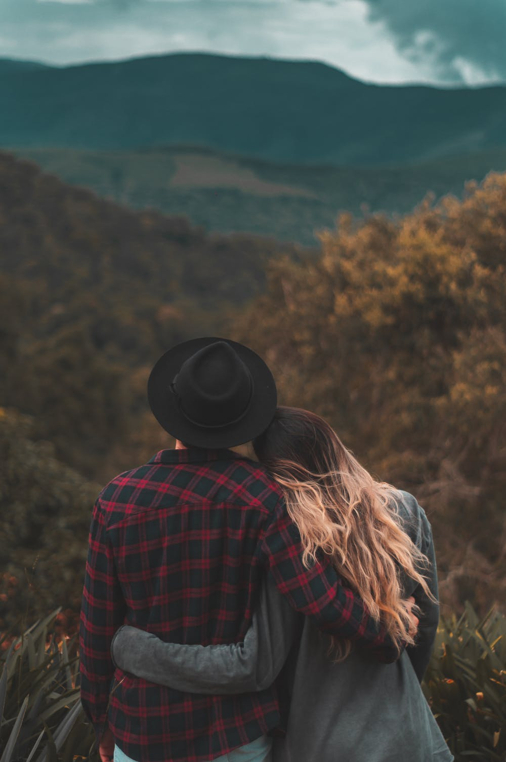 Couple standing on top of hill | Photo: Pexels