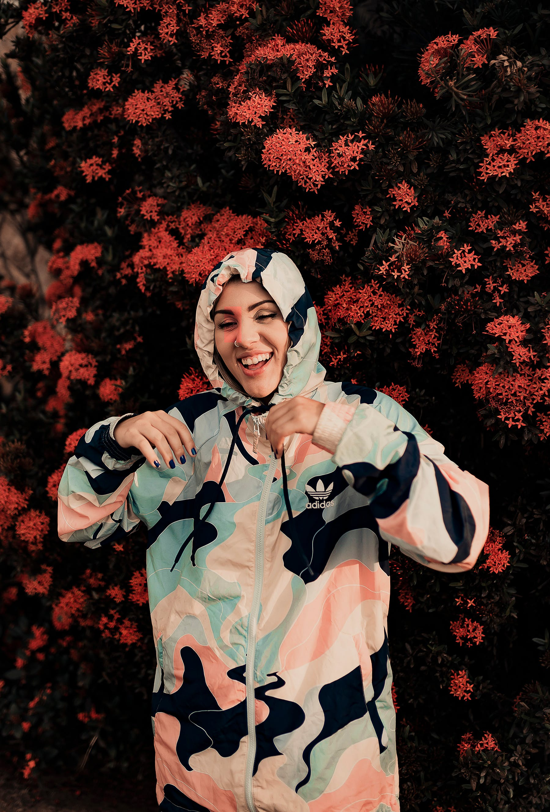 Photo of Woman in Camouflage Hoodie Laughing