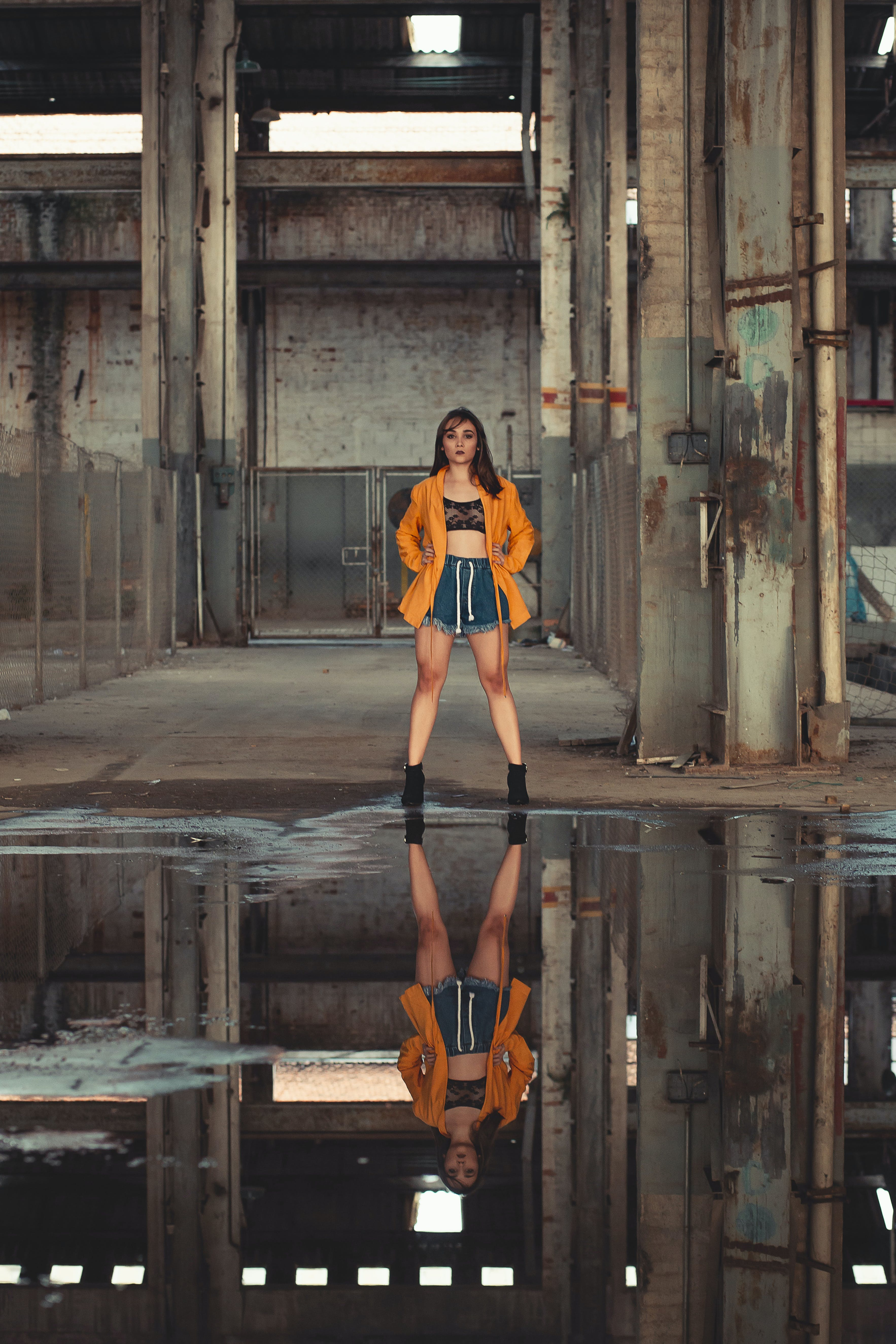 Woman in Orange Blazer Standing in Front of Water Puddle