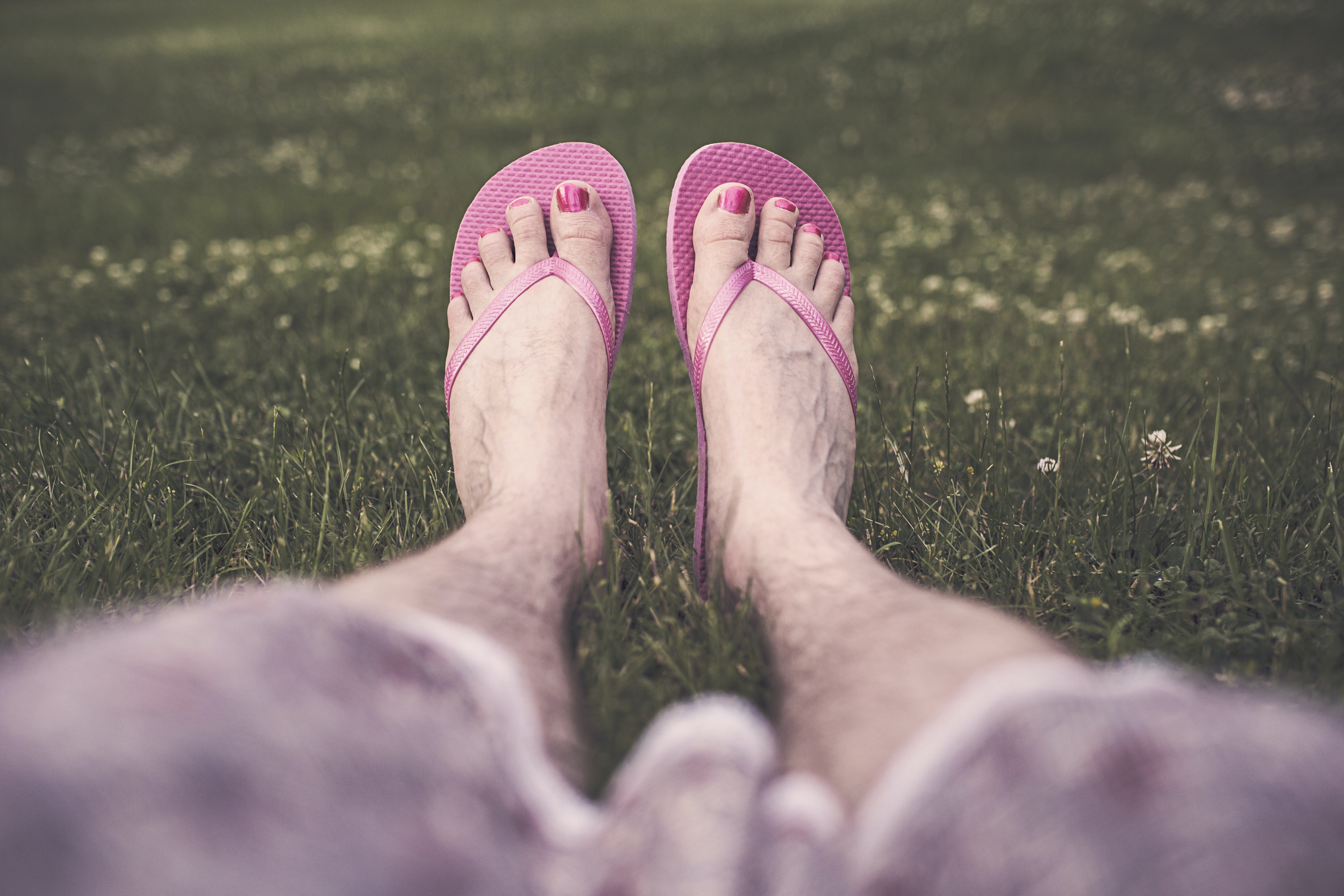 Selective Focus Photography of Person Sitting While Wearing Pair of Pink Flip-flops