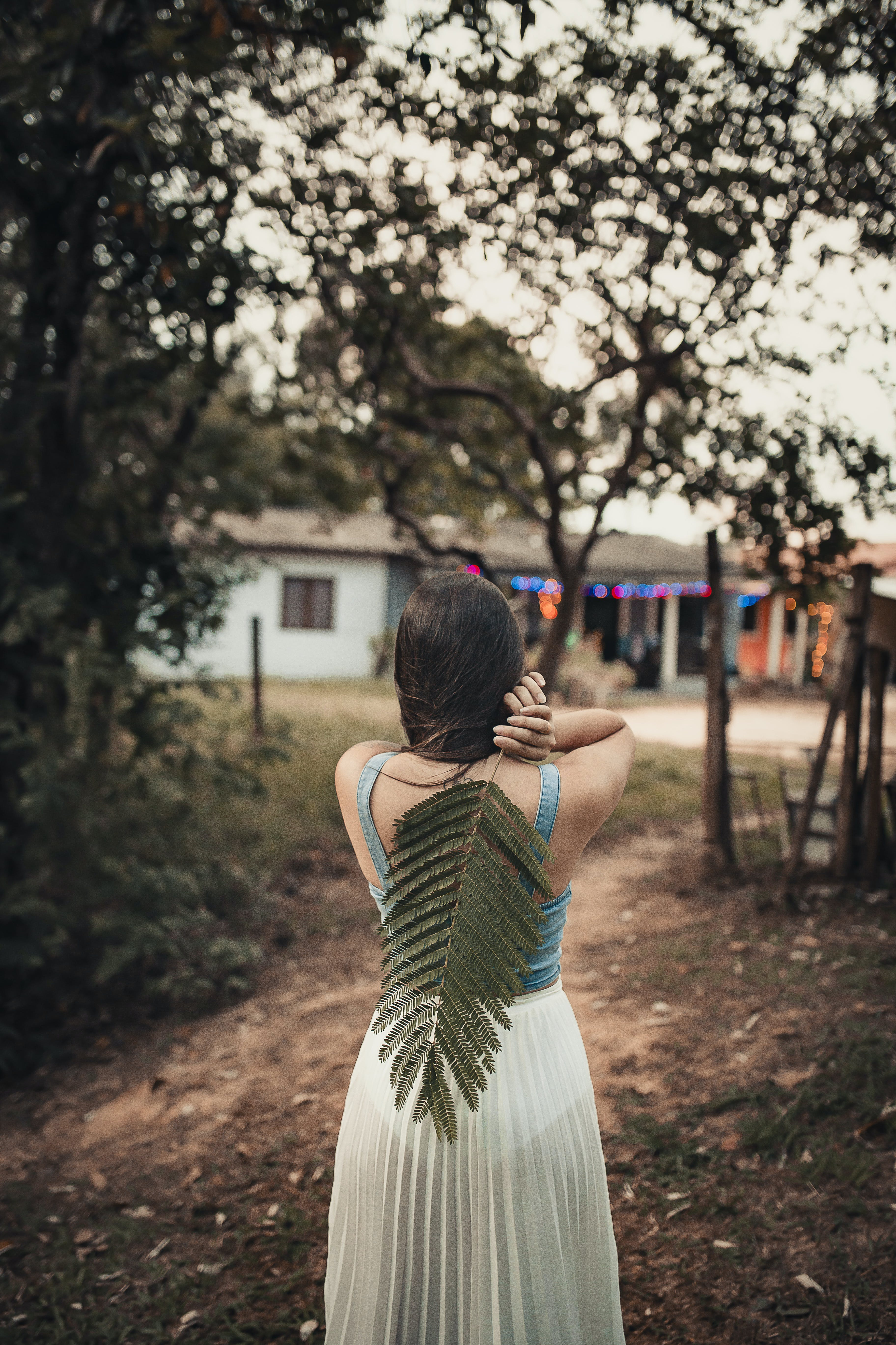 Woman in Sleeveless Dress Holding Large Leaf