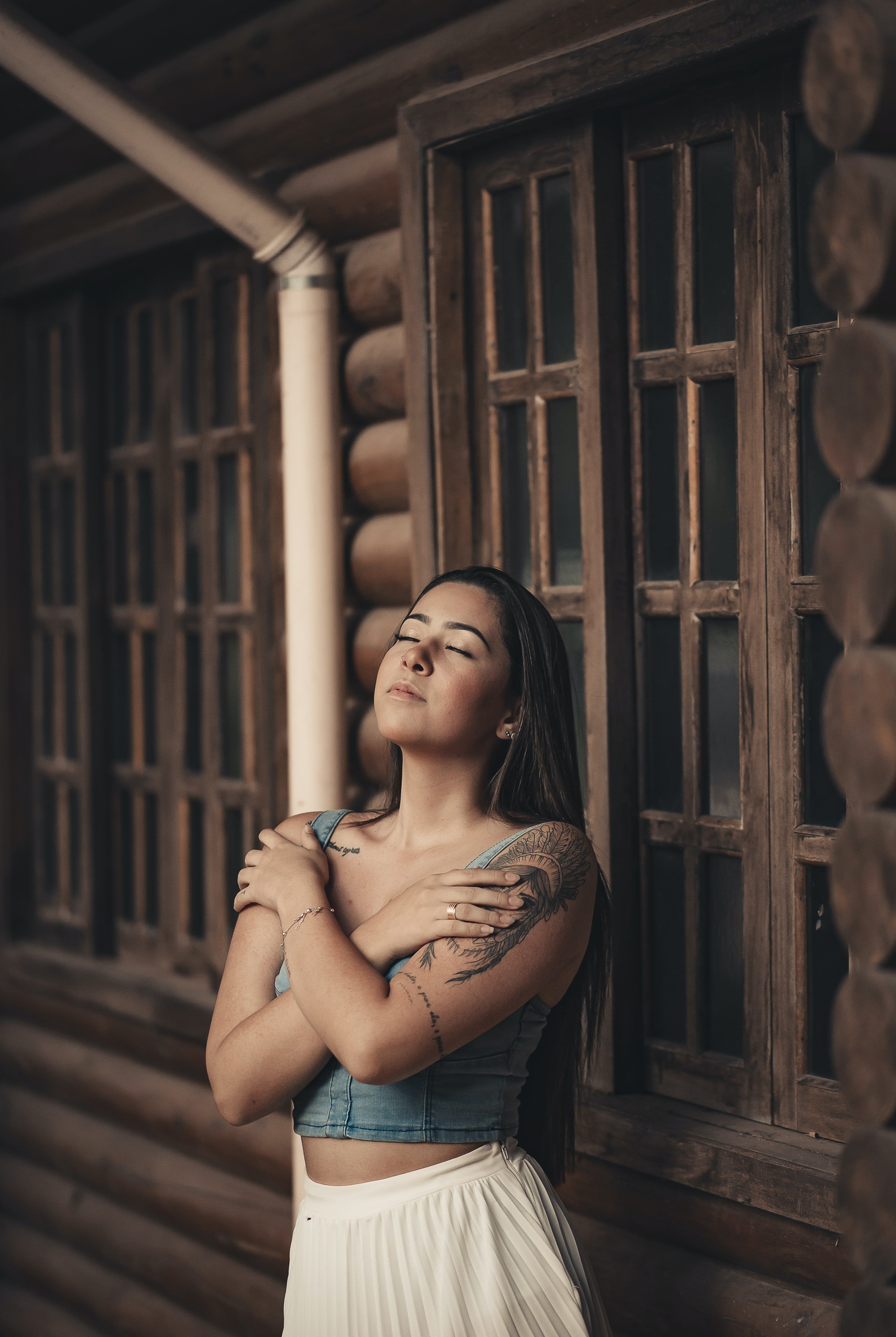 Woman Leaning on Brown Wooden Wall