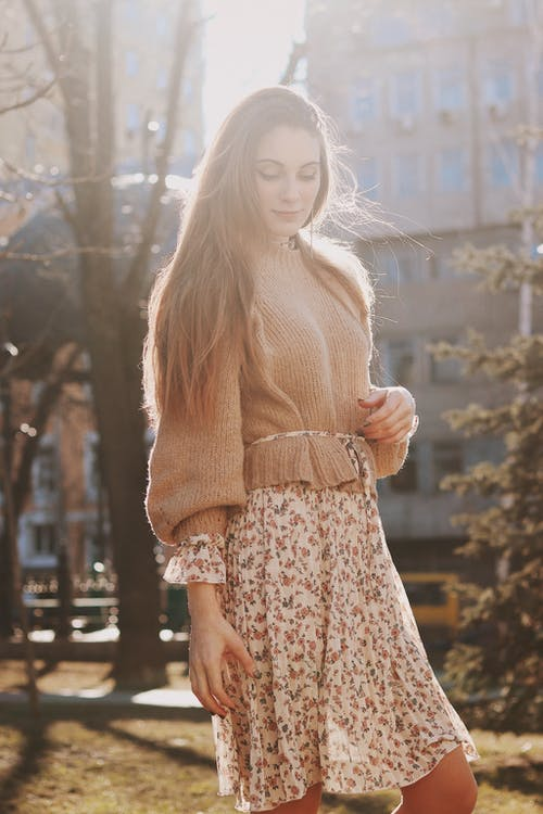 Woman in Beige Knit Sweater and White Floral Skirt in Park