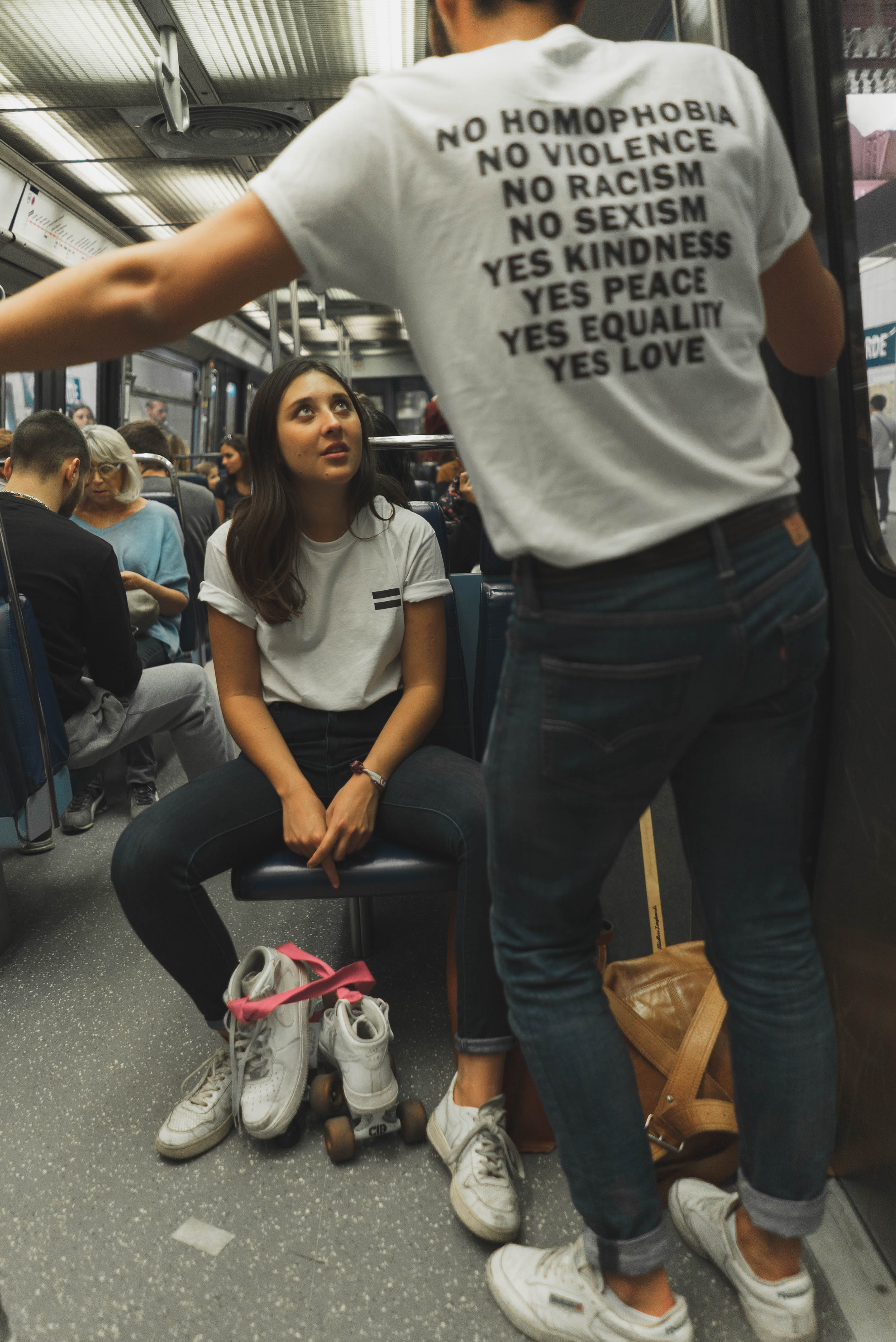 Woman Wearing White Crew-neck Shirt and Black Jeans Sitting on Train Seat
