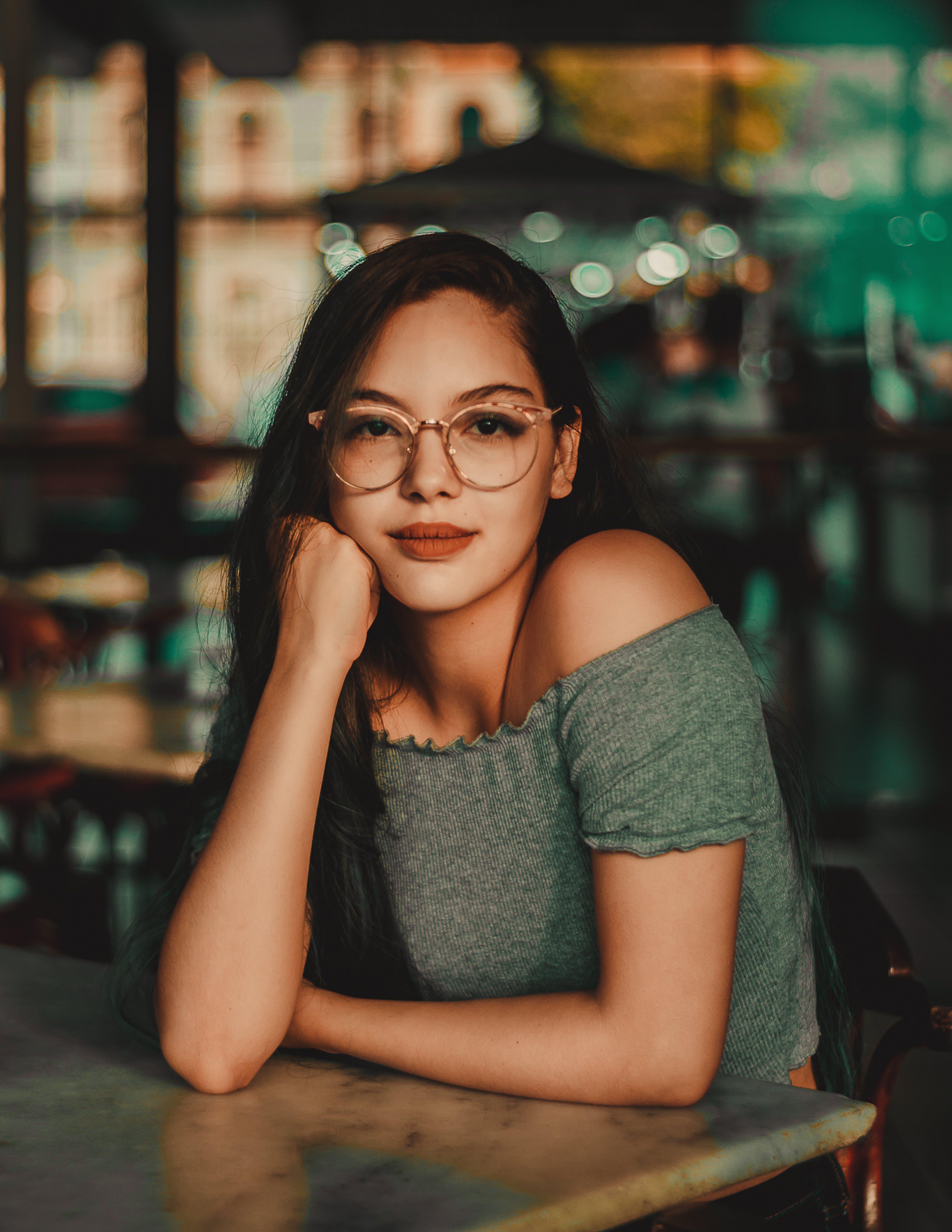 Woman Wearing Eyeglasses Sitting Beside Table