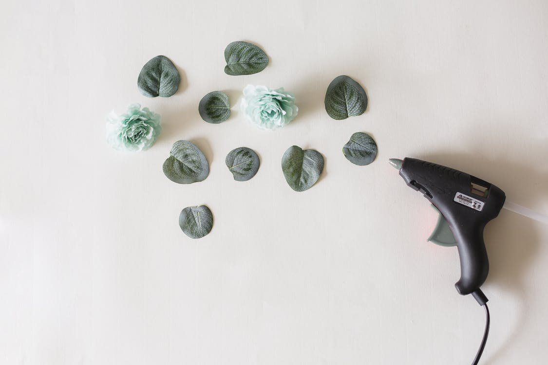 Glue Gun Beside Green Leaves and Flower on White Surface