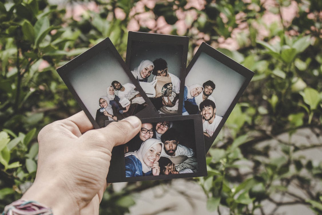 Person Holding Four Family Pictures