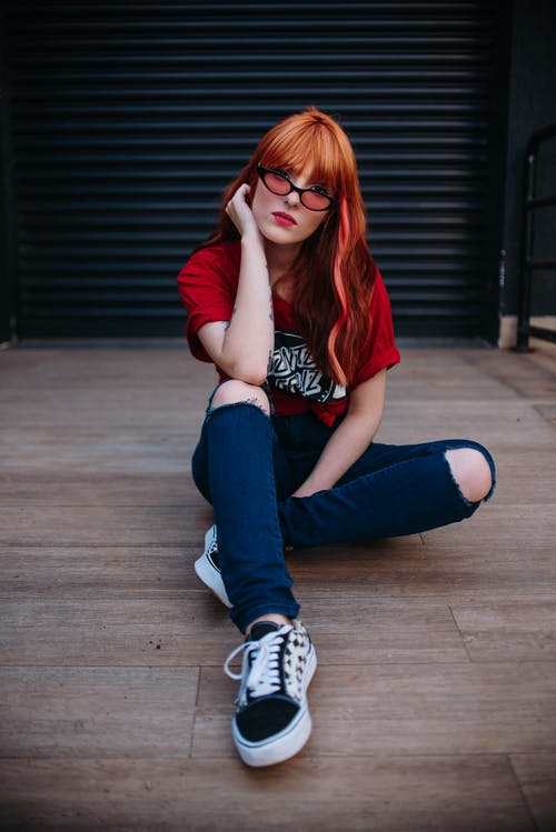 Woman Wearing Red Crew-neck Top Sitting on Brown Plankboard