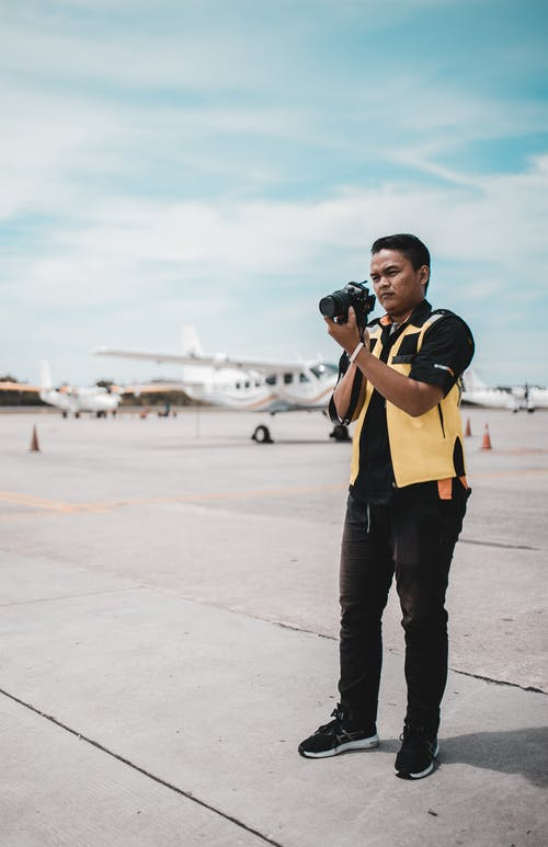 Man in Yellow Vest and Black Shirt Standing on Runway Holding Camera