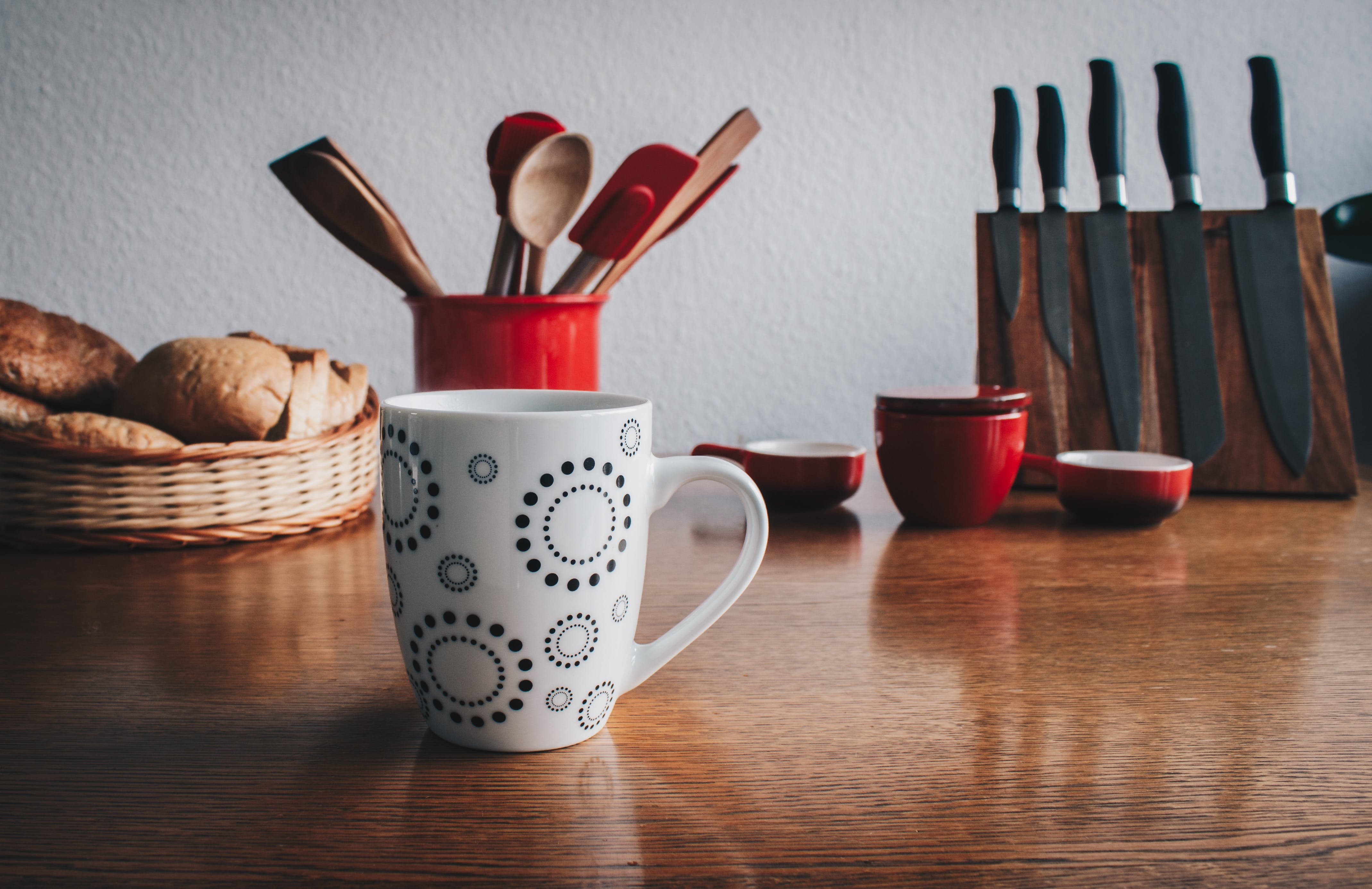 Mug in Front of Breads Beside Spatulas on Table