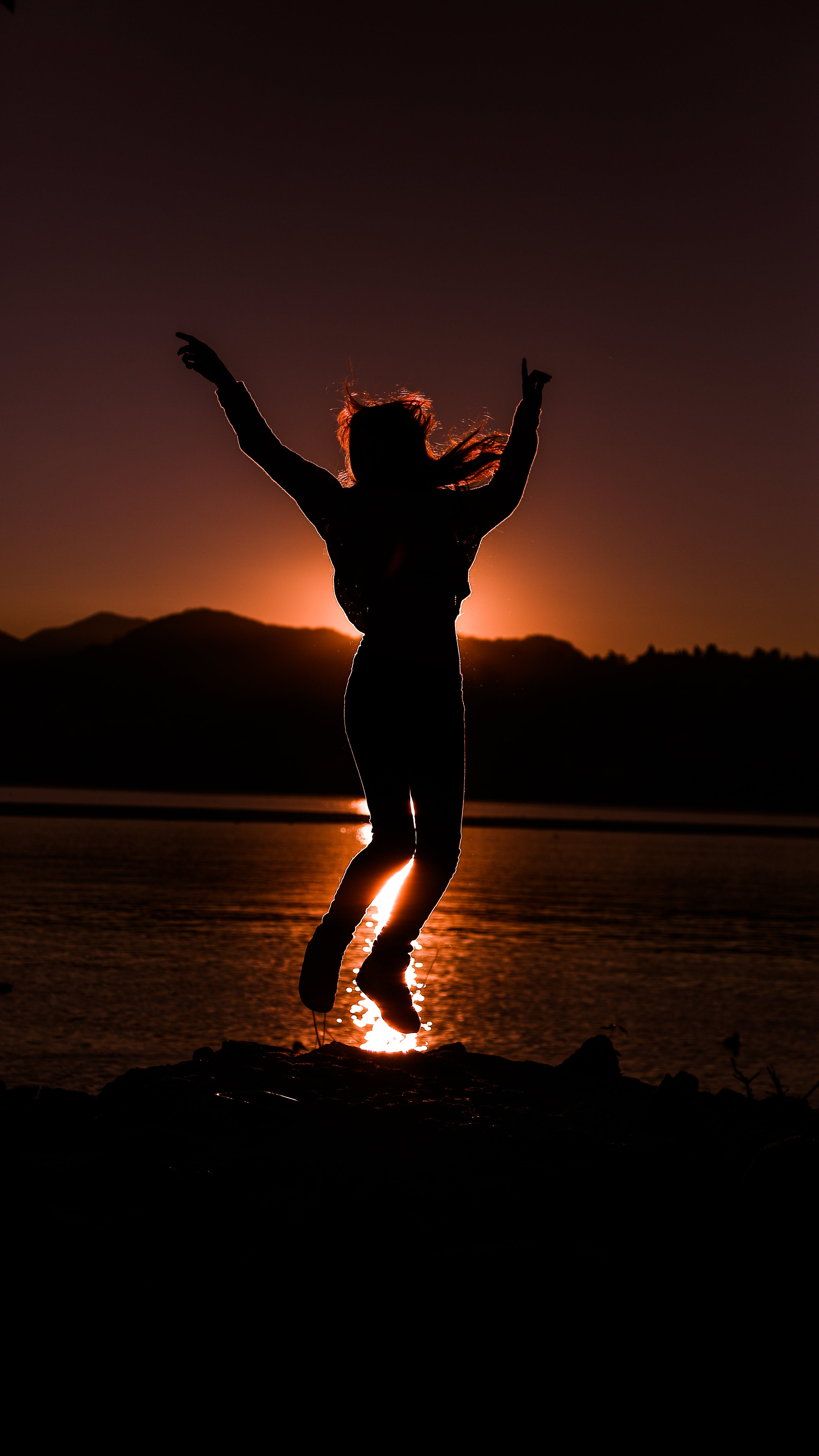 Silhouette of Person Jumping Near Body of Water
