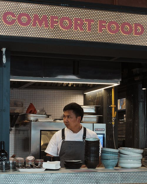 Ethnic male cafe worker at counter with signboard comfort food