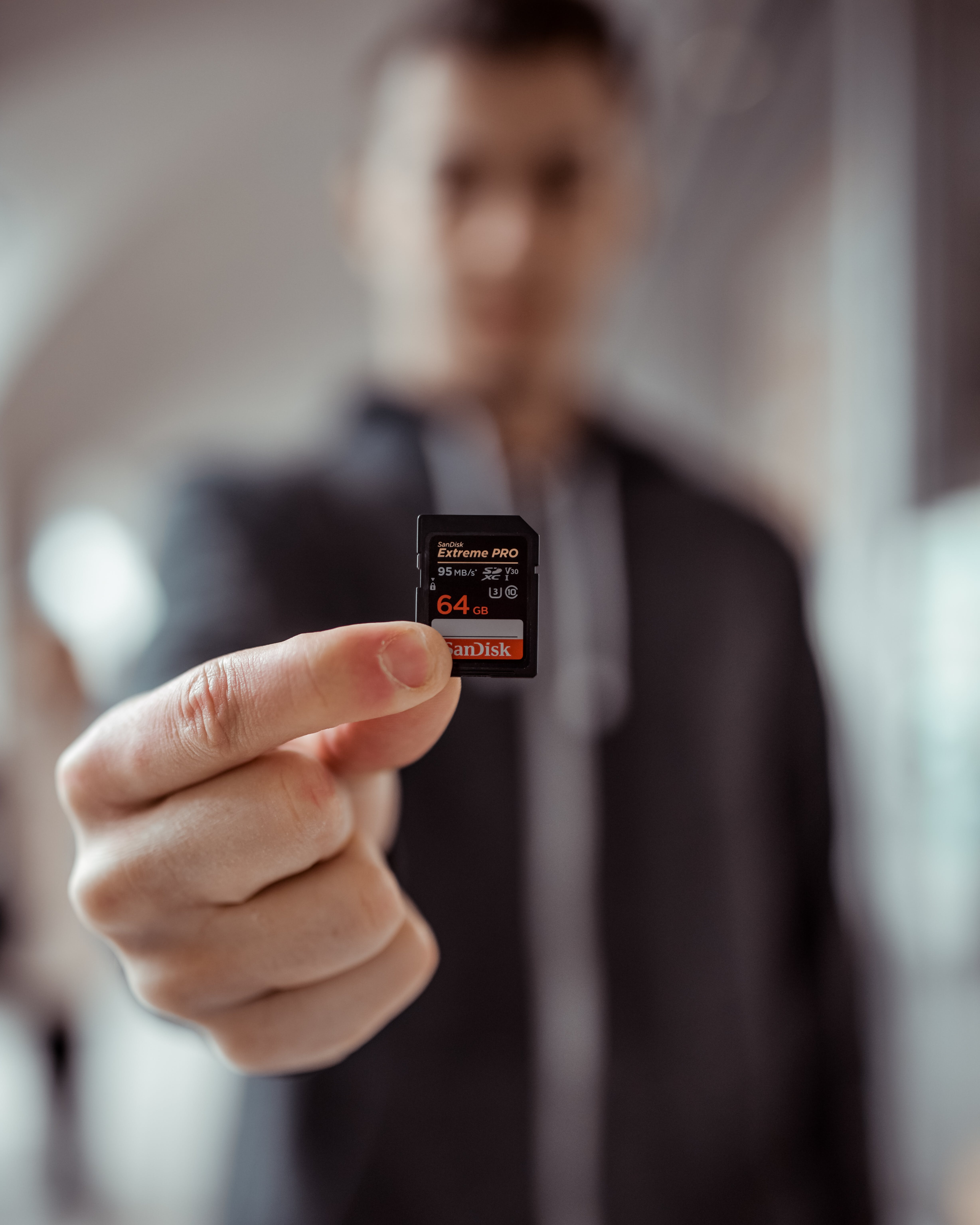 Person Holding Sandisk 64gb Microsd Adapter