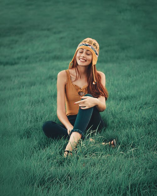 Smiling Woman Wearing Brown Sleeveless Shirt Sitting on Grass Field