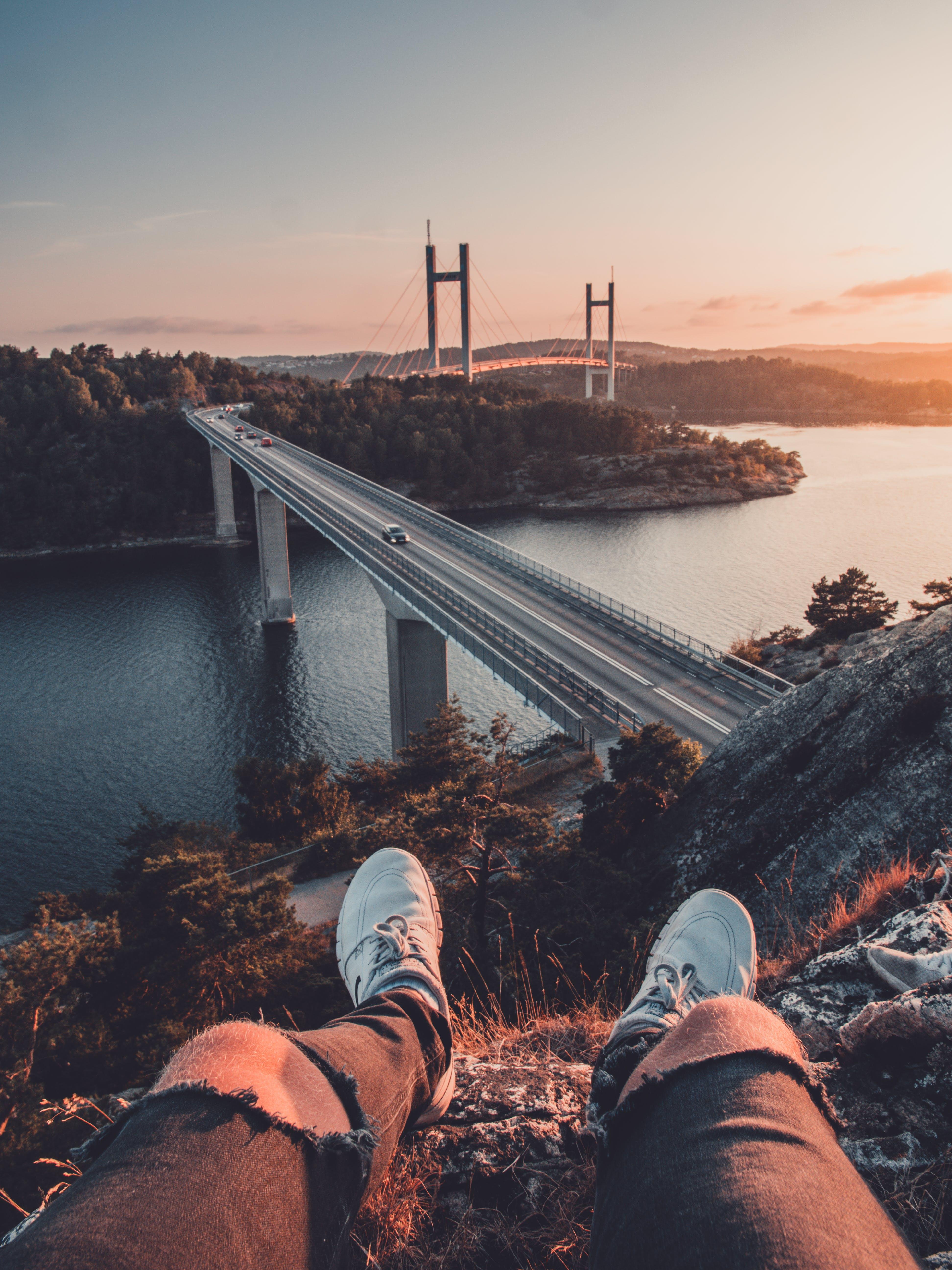 Man Sitting on Rock Near Bridge