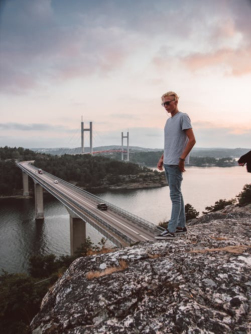 Man Stands on Crest of Hill Overlooking Bridge