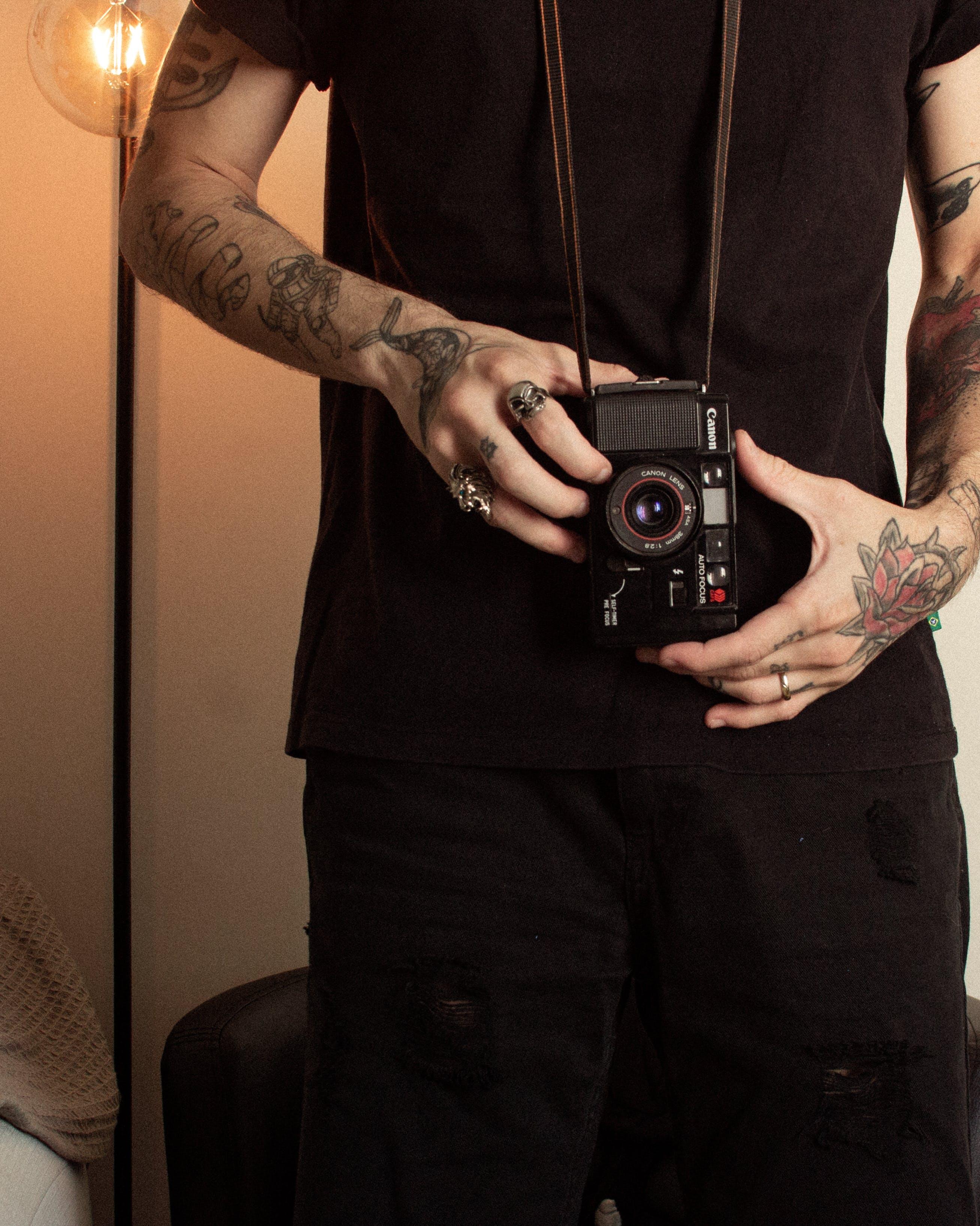 Man Wearing Black Shirt Holding Camera