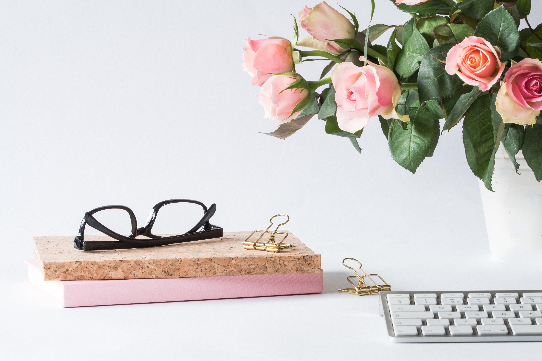 Eyeglasses on Book Beside Rose and Keyboard
