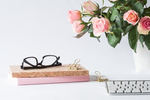 Eyeglasses on Book Beside Rose and Keyboard