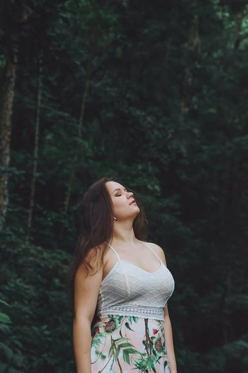 Woman Standing Under Tree Closing Her Eyes While Looking Up