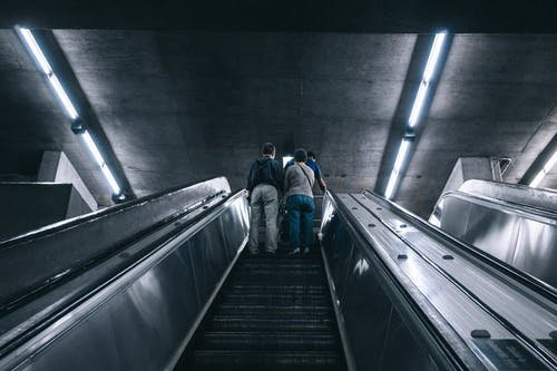 Grayscale Photography of Two Person on Escalator