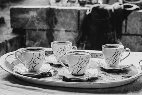 Grayscale Photography of Ceramic Mugs on Saucers
