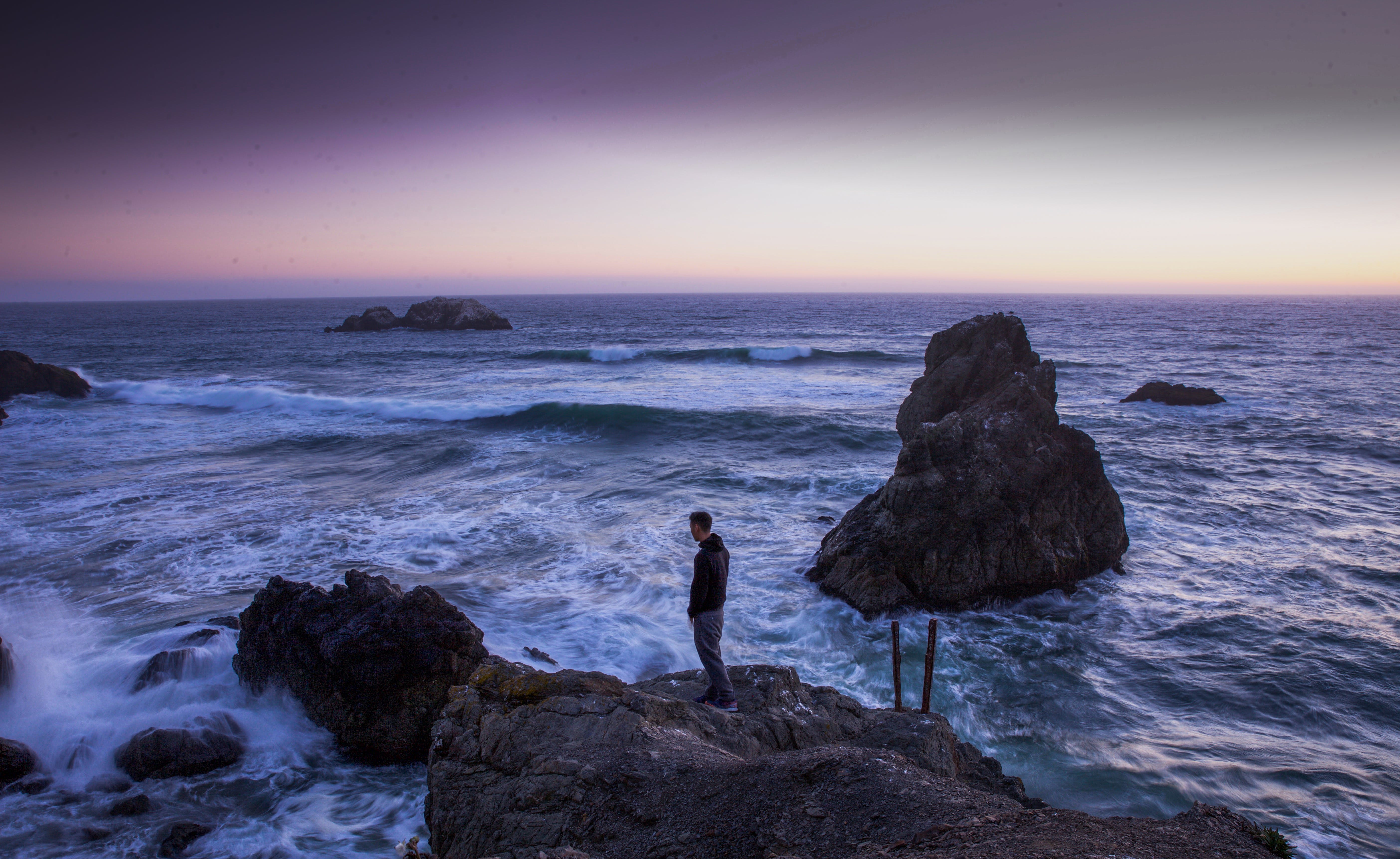 Man in Black Shirt Standing on Rock in Between Sea Water