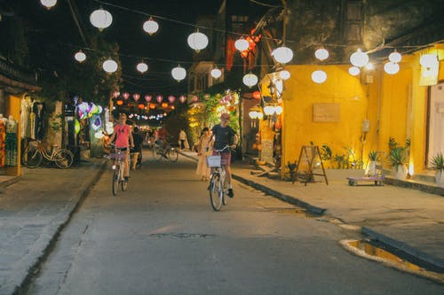 Two Person Riding Bicycle on Road at Night-time