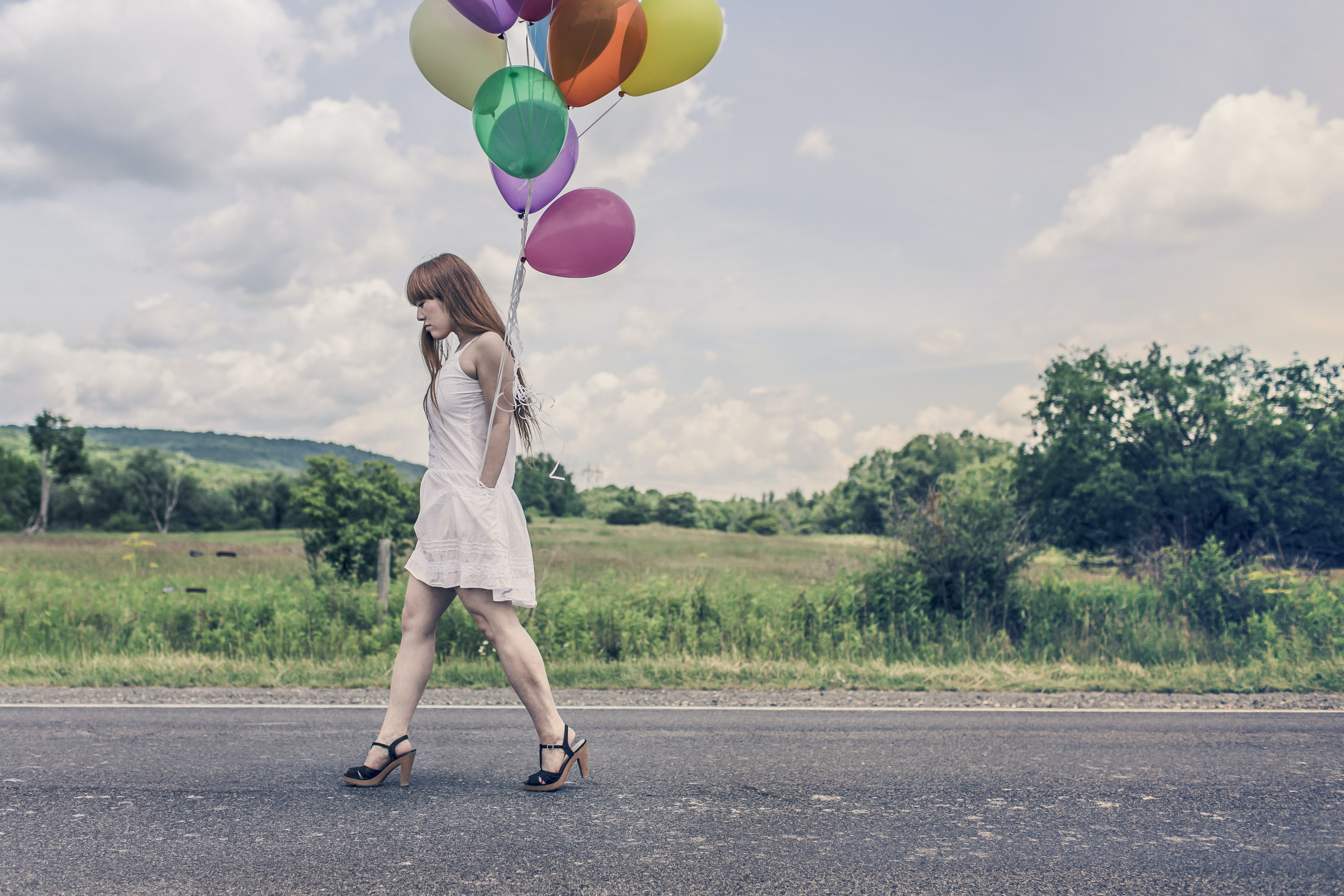 Photography of Woman Walking Near Road Holding Balloons