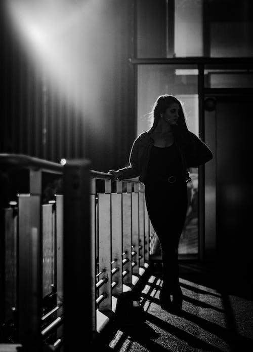 Foto d'estoc gratuïta de baranes metàl·liques, blanc i negre, dempeus, dona