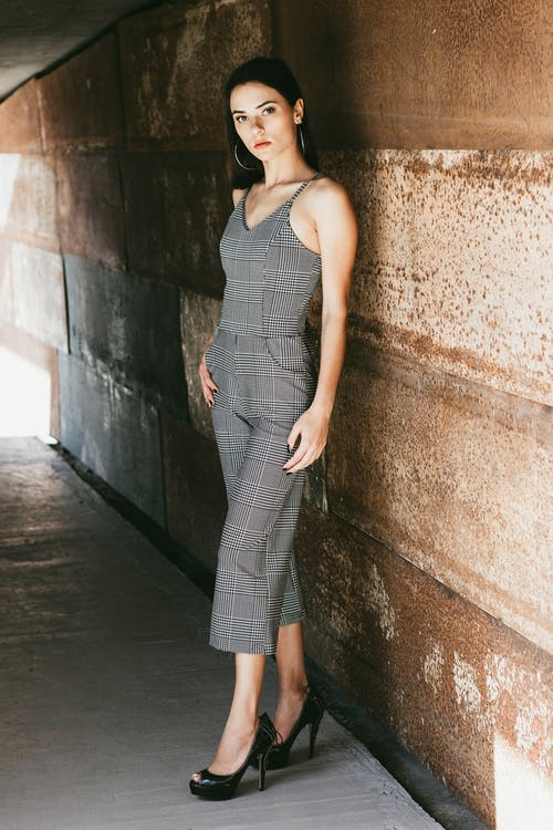 Woman Wearing Grey Sleeveless Dress Standing Near Brown Wall