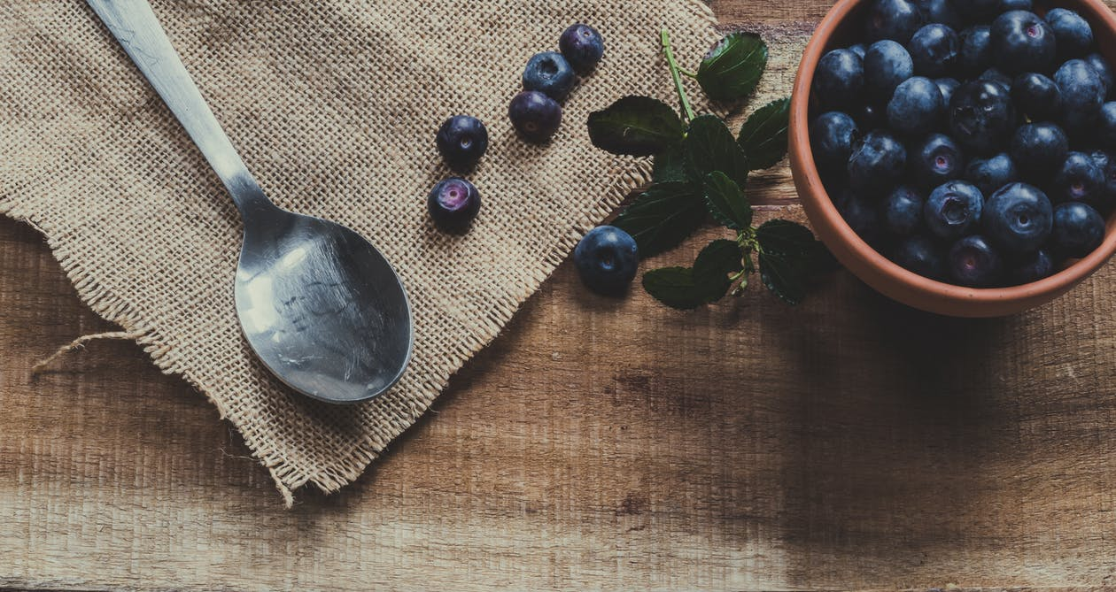 Blueberries on Mug and Brown Surface Near Spoon