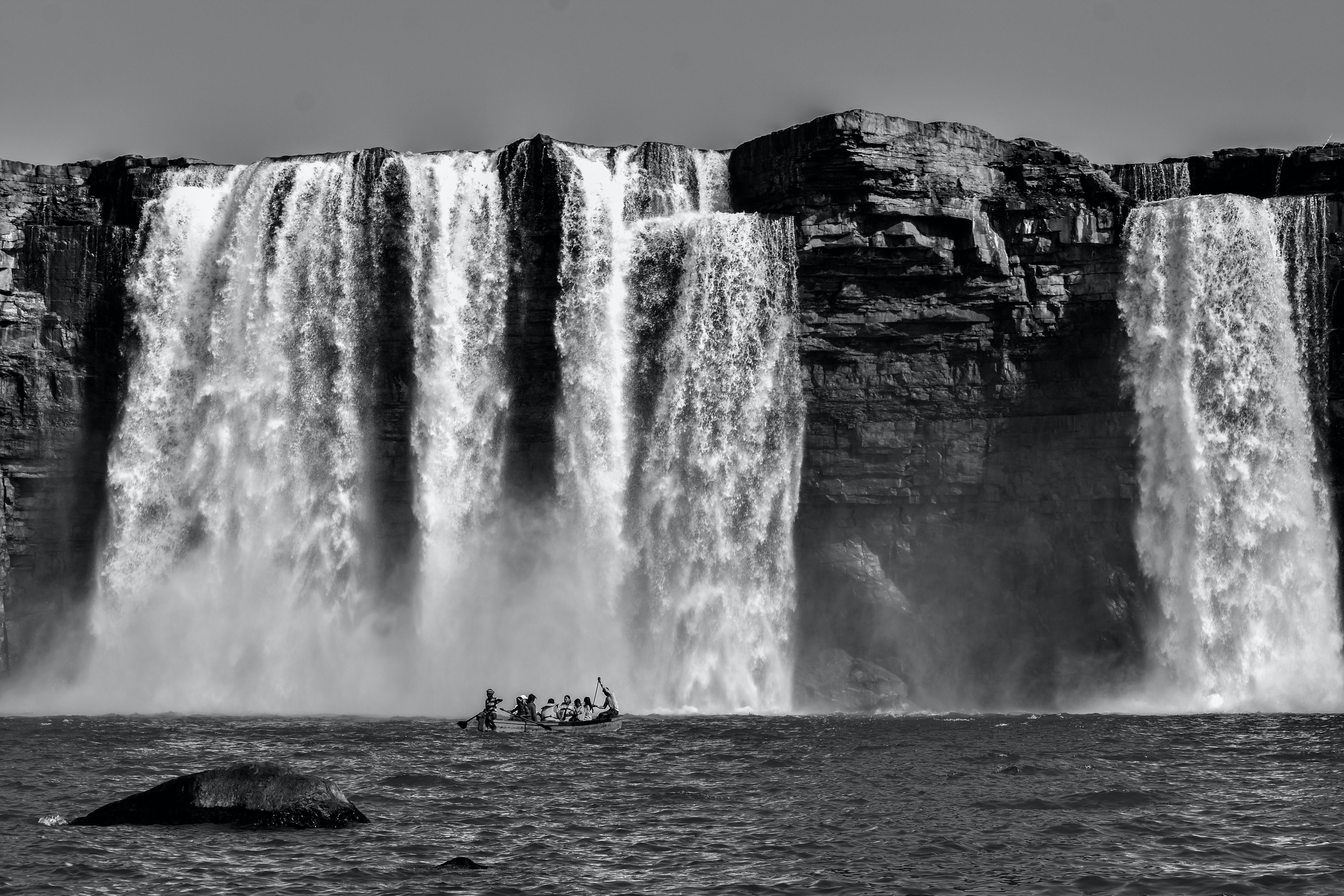 Grayscale Photography Of People Riding A Boat Near Waterfalls