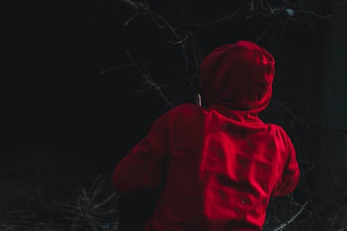 Free stock photo of black background, hoodie, person, red