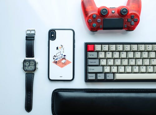 Flat Lay Photography of Dualshock 4 Beside Keyboard, Iphone X, and Digital Watch