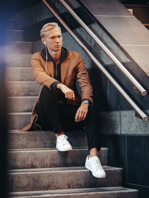 Man in Brown Coat and Black Pants Sitting on Stair