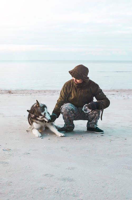 Man Sitting Beside Of Dog