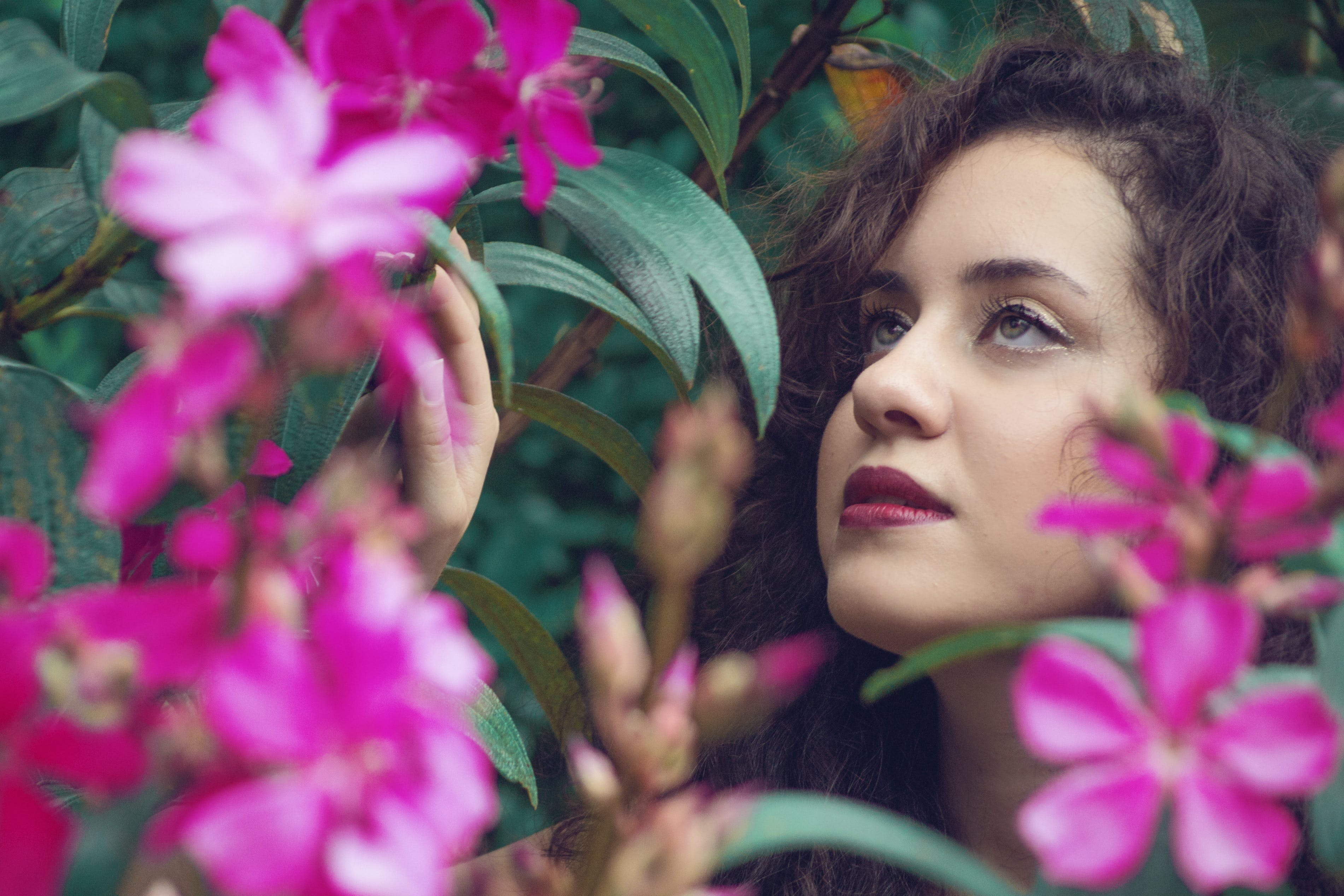 Selective Focus Photography Of Woman Beside Flowers