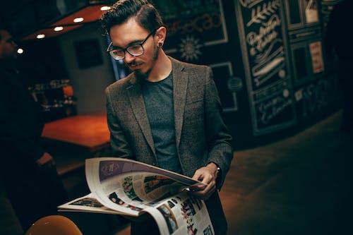 Gratis stockfoto met iemand, kerel, lezen, magazine