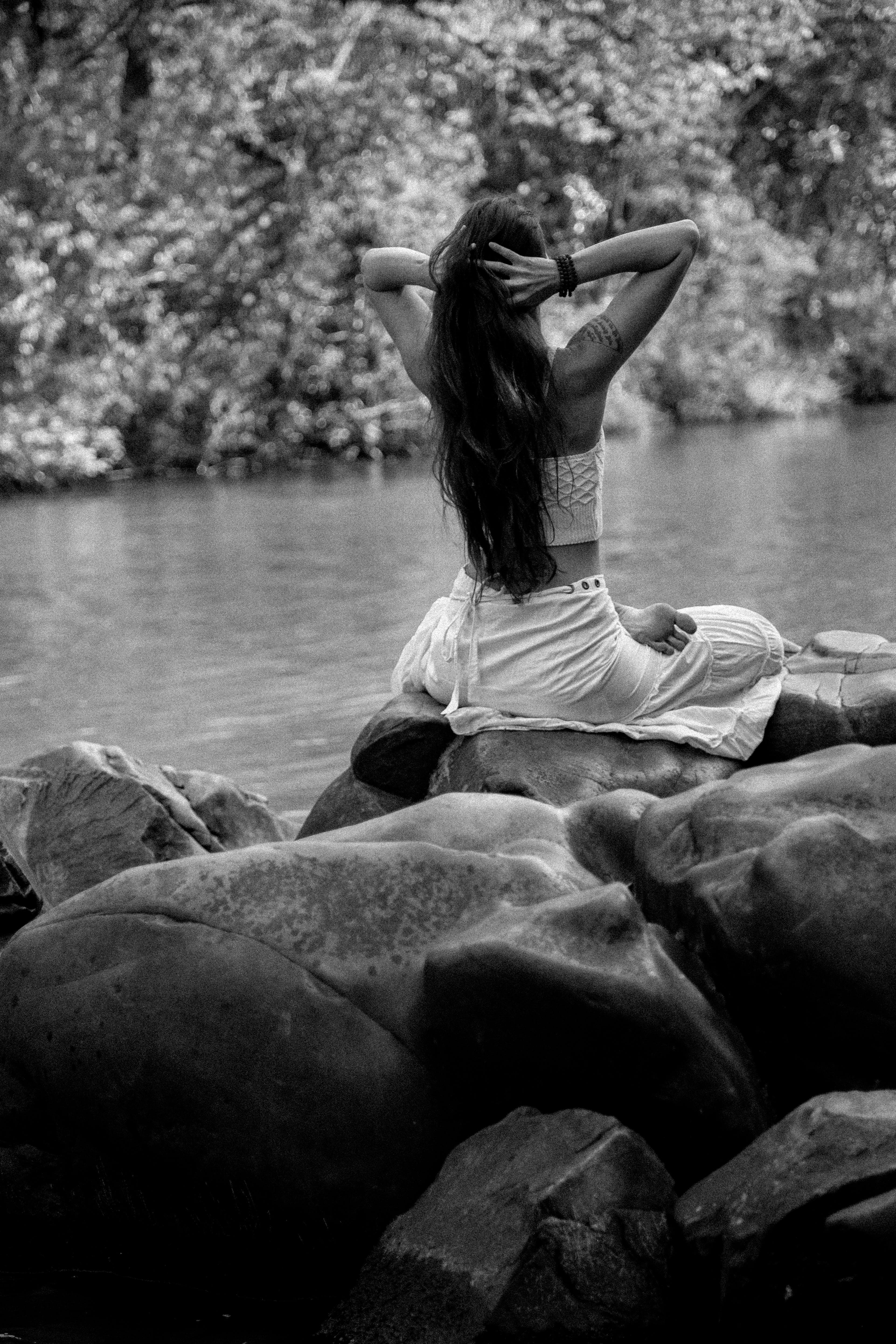 Woman Sitting on Rock Holding Her Head Beside Body of Water