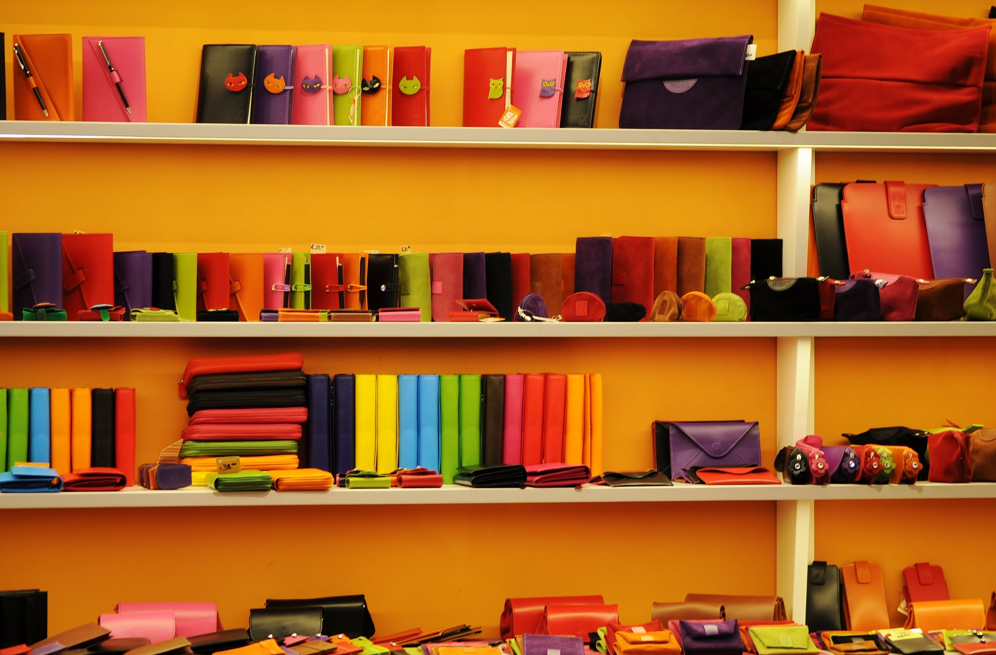 Assorted-color Leather Wallets and Bags on White Shelf